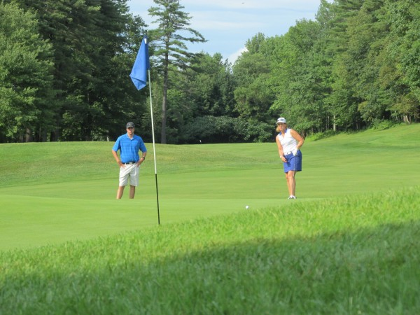 Marla LeBlanc of The Purpoodock Club in Cape Elizabeth watches her putt roll toward the cup on the 15th hole at Waterville Country Club during Wednesday's final round of the Maine Women's Amateur golf tournament. Ben True, the caddie and nephew of Kris Kannegieser, looks on.