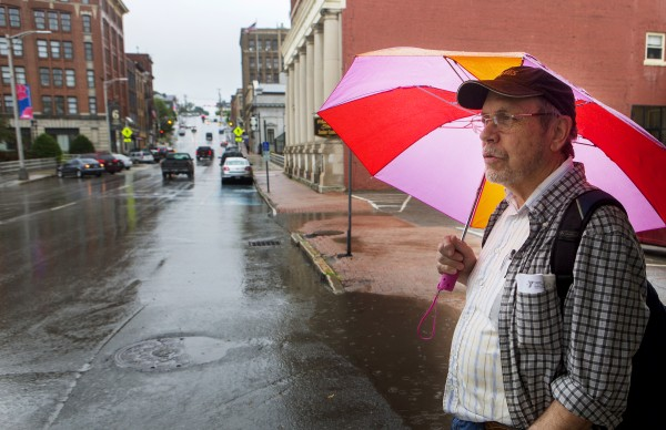Richard Clark stays dry with an umbrella in downtown Bangor during a rainstorm Wednesday.