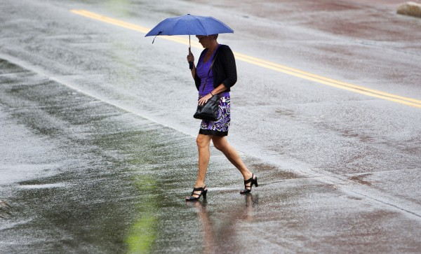 A pedestrian crosses the street in downtown Bangor during a rainstorm Wednesday.
