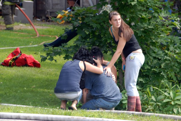 Neighbors huddle around a woman who lost her home to a fire on Depot Street in Mattawamkeag on Thursday, July 31, 2014.