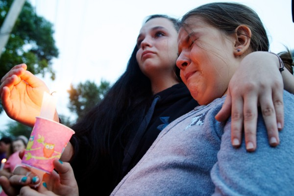 Sierra Tarbox (left), 15, and Alicia Ellis, 9 , grieve at a candlelight vigil Tuesday night outside the Saco apartment where police say 33-year-old Joel Smith shot and killed his wife and three children before killing himself Saturday night.