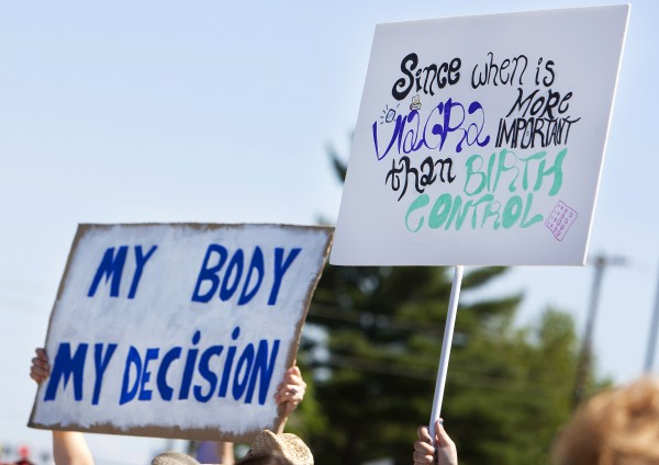 Protestors hold up signs during a protest against the recent Supreme Court decision about birth control on Saturday outside the Bangor Hobby Lobby.