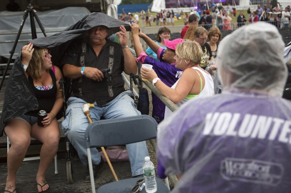 Ashley Brown (left) and Bob Ganem (center) get help with their makeshift rain protection from Mary Ganem (right) during the Boston and Cheap Trick concert Wednesday at Darling's Waterfront Pavilion in Bangor.