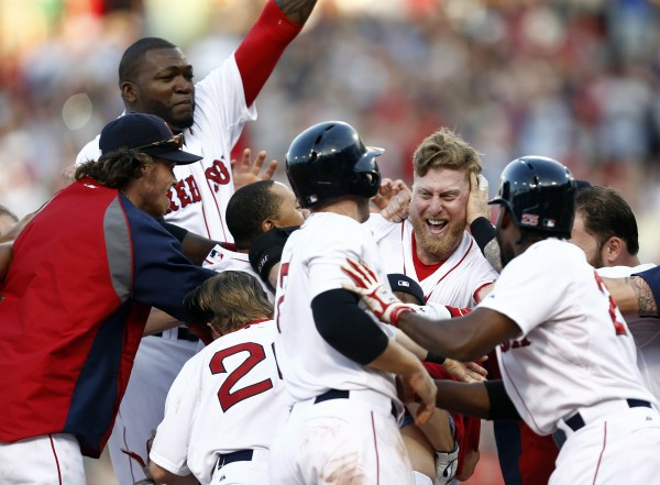 The Boston Red Sox mob Mike Carp (third from right) after he singled in Daniel Nava with the winning run against the Chicago White Sox during the 10th inning Thursday at Fenway Park in Boston. The Red Sox won 4-3.