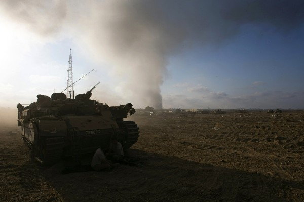 Smoke rises after an explosion in Gaza as an Israeli armored personnel carrier is parked at a staging area near the border with Gaza July 23, 2014.