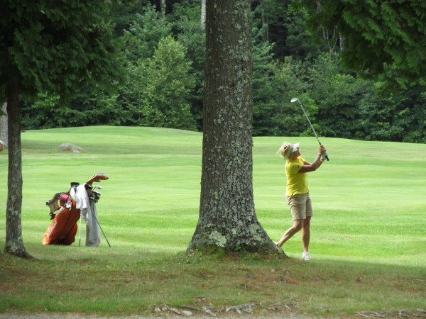 Debby Gardner of Waterville Country Club hits her approach shot from under a tree on the 13th hole at her home course during the Maine Women's Amateur golf tournament on Tuesday.