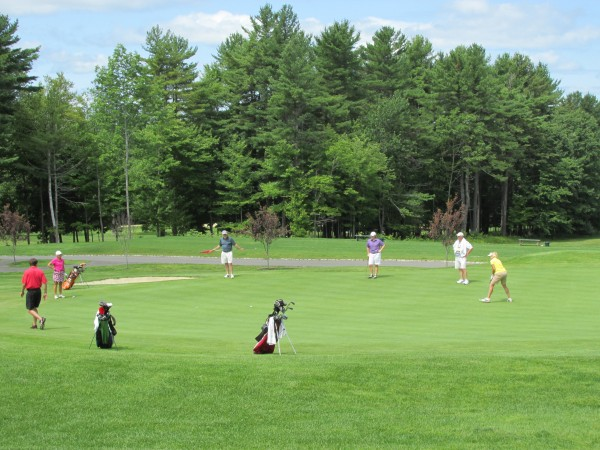 Players and their caddies line up their putts on the green during the Maine Women's Amateur golf tournament on Tuesday at Waterville Country Club in Oakland.