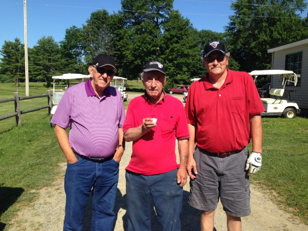 Ed Nickerson (center) of Stockton Springs holds up his golf ball after recording a hole-in-one Saturday on the sixth hole at Hampden Country Club. Looking on are playing partners Paul Bertrand (left) and Cory Brooks of Old Town.