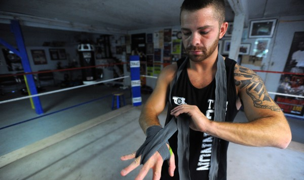 Boxer Brandon Berry of West Forks puts on his hand wrap before a workout at Wyman's Boxing Club in Stockton Springs. Berry said that being from a small town is not a disadvantage, and he enjoys working out at the small club with people who have different skill levels.
