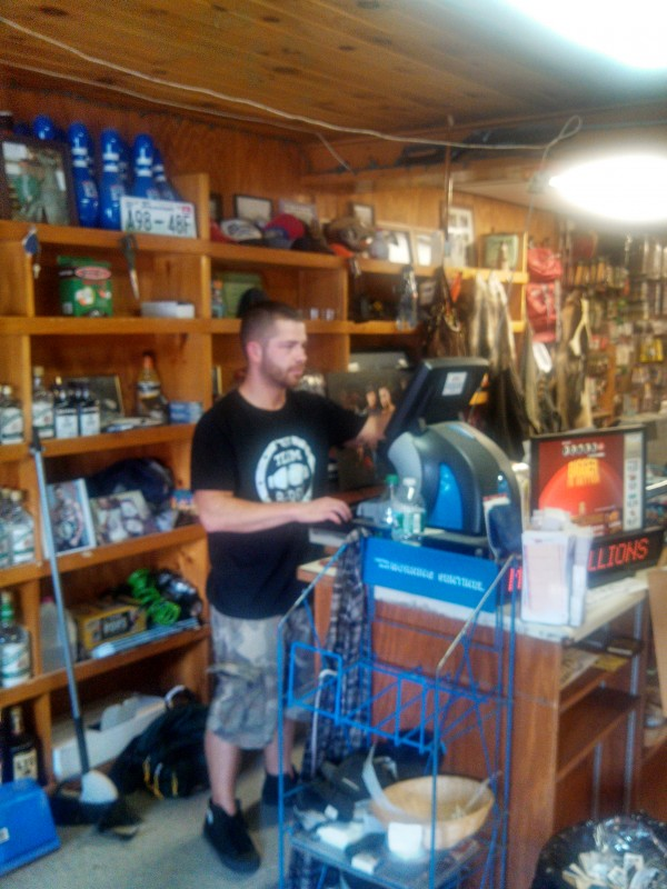 Brandon Berry tends to the cash register on July 7 at his family's general store in West Forks, Maine.