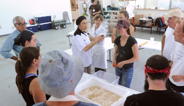 Production workshop participants listen to instructions from Sharon Burns-Leader (center, with black hat), owner of Bread Alone Bakery in Kingston, New York, during the 2014 Kneading Conference in Skowhegan on Friday.