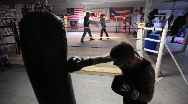 Boxer Brandon Berry of West Forks (foreground) works out at Wyman's Boxing Club in Stockton Springs while gym owner Ken &quotSkeet&quot Wyman (background left) works with 13-year-old Ashten Wells of Searsport.  Berry said that being from a small town is not at all a disadvantage, and he enjoys working out at the small club with people who have different levels of experience in boxing.