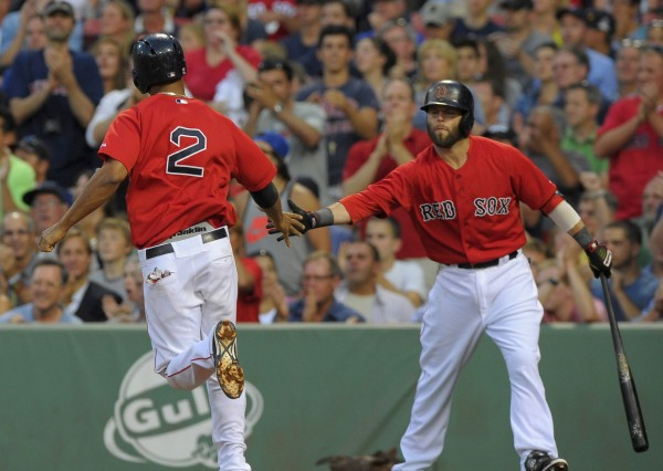 Boston's Dustin Pedroia (15) congratulates Xander Bogaerts (2) after scoring a run during the second inning against the Kansas City Royals at Fenway Park in Boston Friday night. The Red Sox won 5-4.