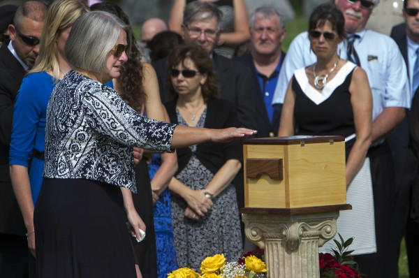 Dora Winslow touches the urn of her late husband, former Bangor police chief Don Winslow, Thursday at Mount Pleasant Cemetery.