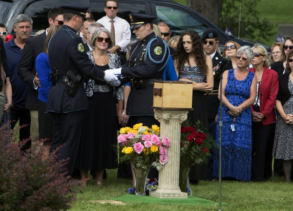 Members of the Bangor police department present Dora Winslow with an American flag during the funeral of her late husband, former Bangor police chief Don Winslow Thursday at Mount Pleasant Cemetery.