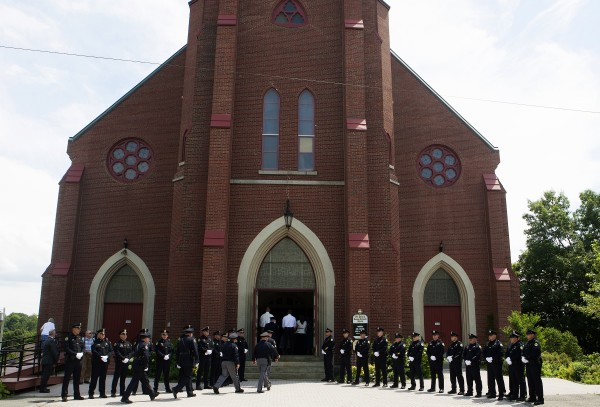 Around 30 Bangor police officers line up to pay their final respects to former Bangor police chief Don Winslow Thursday outside of St. John's Catholic Church.