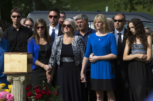Dora Winslow, center, is comforted by family during the burial of her late husband, former Bangor police chief Don Winslow Thursday.