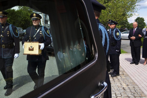 Bangor police officers place the remains of former Bangor police chief Don Winslow into the back of the hearse Thursday outside of St. John's Catholic Church.