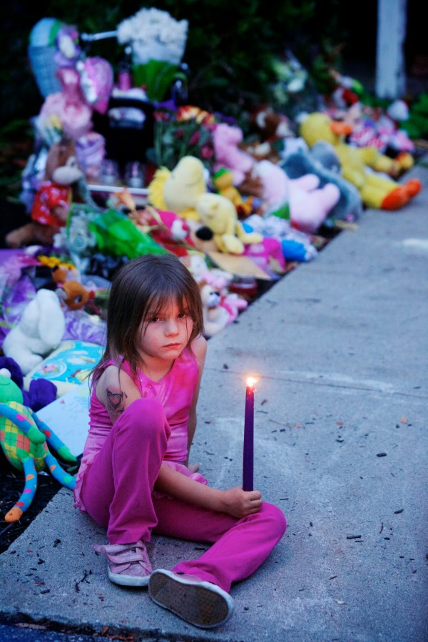 Payton Cavallaro, 6, holds a candle in memory of her neighbors Tuesday night outside the Saco apartment where police say 33-year-old Joel Smith shot and killed his wife and three children before killing himself on Saturday night.