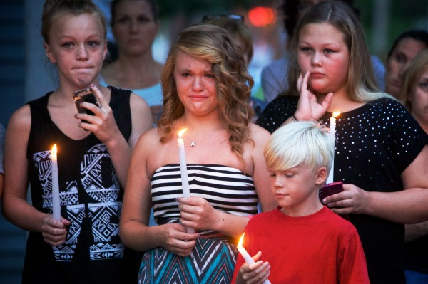 Friends (from left) Lyric Twohig, 12, Adrianna Grimaldi, 12, and Janet Olson, 11, hold candles at a vigil Tuesday night outside the Saco apartment where police say 33-year-old Joel Smith shot and killed his wife and three children before killing himself on Saturday night.