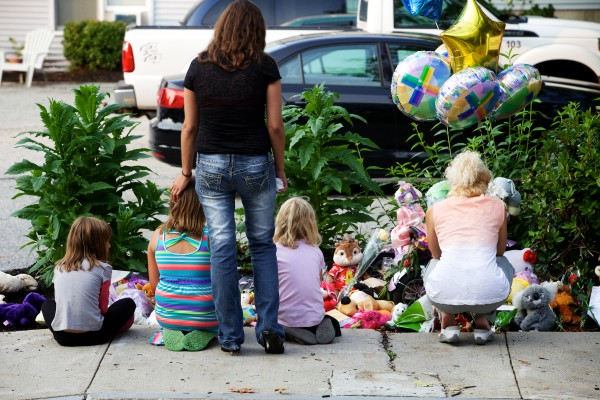 Mourners pause by a makeshift shrine Tuesday night outside a Water Street apartment in Saco where police say 33-year-old Joel Smith shot and killed his wife, Heather Smith, 35, his stepson, 12-year-old Jason Montez, and two biological children, Noah Montez, 7, and Lily Smith, 4, before killing himself.