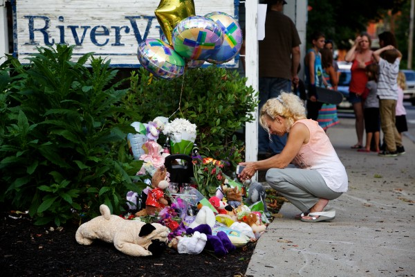 Jackie Koller prays near a makeshift shrine on Water Street in Saco on Tuesday night where her co-worker, Heather Smith, 35, was killed, along with her three children, by her husband Saturday night.
