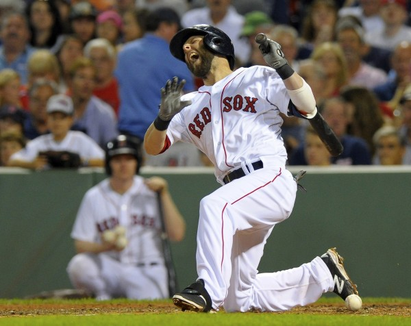 Boston's Dustin Pedroia (15) reacts after fouling a ball off his foot during the fifth inning against the Toronto Blue Jays at Fenway Park in Boston Tuesday night.