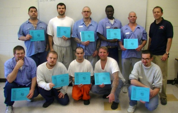 Michael Fournier, Maine Dept of Corrections, recreational therapist for InsideOutDads program, stands (wearing a navy blue polo shirt, in the upper right of the photo) with the program's first graduating class.