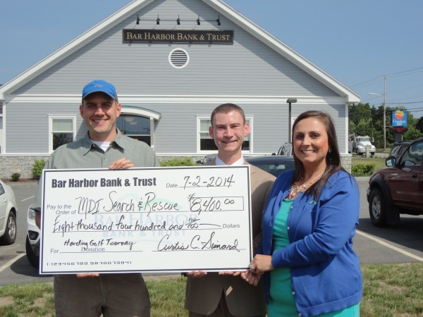 Davin O'Connell of MDI Search and Rescue accepts a check for $8,400 from Dylan Mooney and Krystal Jordan of Bar Harbor Bank & Trust, representing the planning committee for the Bank's 21st Annual David R. Harding Memorial Charity Golf Tournament played at Kebo Valley Golf Club on June 3.