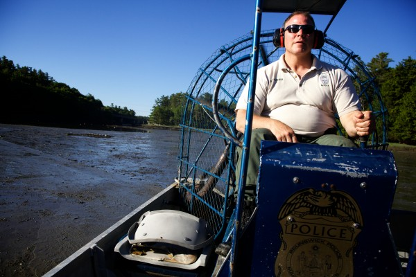 Brunswick Marine Resources Officer Dan Devereaux steers an airboat after checking a trap designed to catch invasive green crabs in Buttermilk Cove on Friday morning. The traps are part of a study designed to figure out the best way to defend valuable clams from the voracious crustaceans.