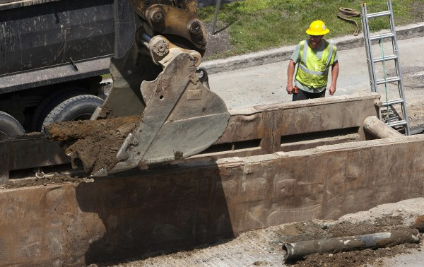 A backhoe digs out old piping Tuesday near the intersection of Main Street and Buck Street in Bangor.
