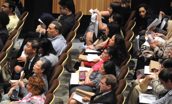 New U.S. citizens listen during a Naturalization Ceremony at the Gracie Theater at Husson University in Bangor on Thursday.