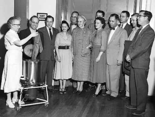 The executive board of the Penobscot County Chapter of the National Foundation for Infantile Paralysis visited the Eastern Maine General Hospital in December of 1953 and saw some of the polio treatment equipment demonstrated. Miss Florence Orr, head of the physio-therapy department, demonstrates the hot-pack machine. Looking on, (front row, from left) are Miss Orr, Sidney Alpert, Earle Brown Jr., Mrs. Carl E. Libby, Mrs. Wilbur Chadeayne, Mrs. Warren S. Overlock, C. Everett Page, Winslow Grant and Eugene McCarthy. (Back row) John E. Coney, John Flynn and Gerald Rudman.