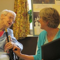 Sarah Fahey talks with Candy Russell, Executive Director of the Moosehead Historical Society, after receiving the cane.