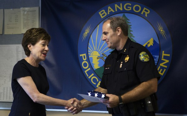 Sen. Susan Collins (left) presents Bangor Police Chief Mark Hathaway a flag that flew over the Capitol in memory of former Chief Don Winslow Friday at the Bangor Police Department.
