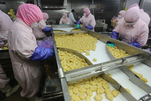 Employees work at a production line prior to a seizure conducted by officers from the Shanghai Food and Drug Administration, at the Husi Food factory in Shanghai, July 20, 2014. A watchdog closed Shanghai Husi Food Co Ltd, a local unit of OSI, and seized meat products suspected of being beyond their expiration date, according to a statement on Monday from the Shanghai Municipal Food and Drug Administration.