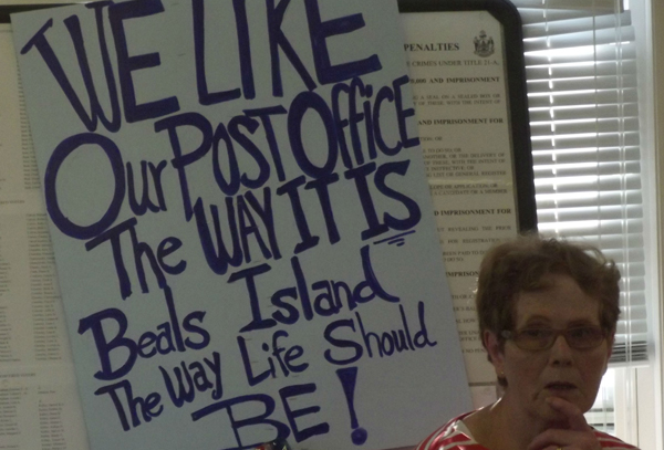 A sign next to Shirley Beal expresses the view held by islanders who showed up at the town office to meet with a Postal Service official Monday. The Postal Service is considering reducing the hours of the town's post office, where all residents have to pick up their mail.
