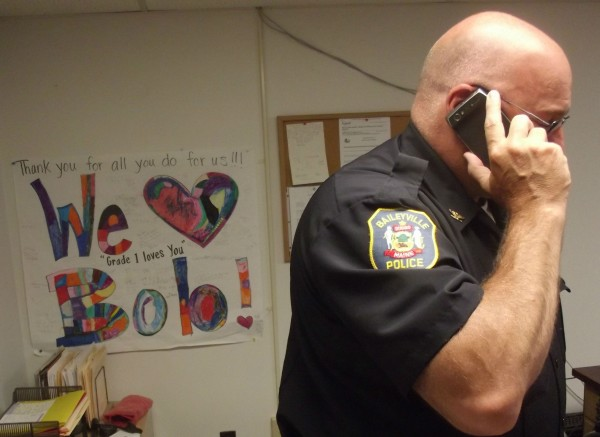 Baileyville Police Chief Bob Fitzsimmons takes a cellular phone call in his office. Poster at left, emblazoned with 'Grade 1 loves you,' was from students at Woodland Elementary School.
