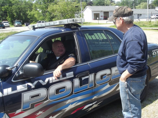 Baileyville Police Chief Bob Fitzsimmons takes a few minutes to talk with Jack Costello. Costello had appeared ill the previous day and Fitzsimmons called for an ambulance to get him checked out.