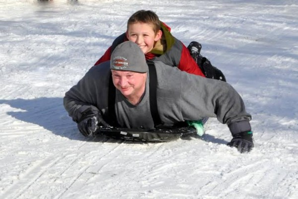 Riley Cleghorn catches a ride atop Baileyville Police Chief Bob Fitzsimmons during a day of sledding the chief organized this past winter.