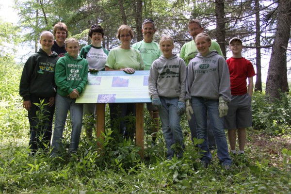 Participants in the Kennebec Savings Day of Caring gathered around the Viles Arboretum Larch Collection interpretive sign for a group shot. Amada Jorgensen (leaning on sign), Talia Jorgensen (green Brut squad sweatshirt), Mindy Jorgensen, Mary Hammond, Judy Johnston, Mark Johnston, Tessa Jorgensen, Todd Jorgensen, Tara Jorgensen, Ethan Hammond.