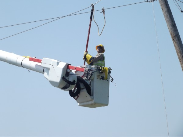 Bob McAllister, a lineman for Emera Maine, attaches equipment to ground power lines in Machiasport on Tuesday so other workers can safely remove a tree that fell onto lines nearby.
