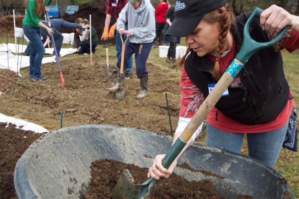 Brandy Stewart (front) and other volunteers help install the new community garden.