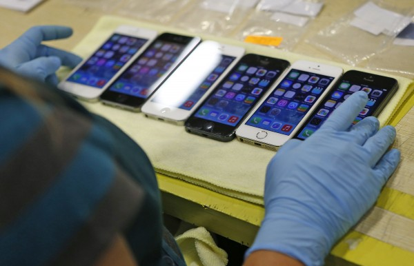 iPhones by the hundreds are lined up after being repaired, reloaded with software and polished, each having its functions checked Aug. 7, 2014 at GameStop's refurbishment center in Grapevine, Texas.