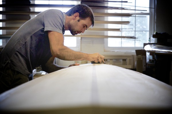 Luke Cushman planes an 8'6&quot wooden surfboard in his shop at his home in Old Town.