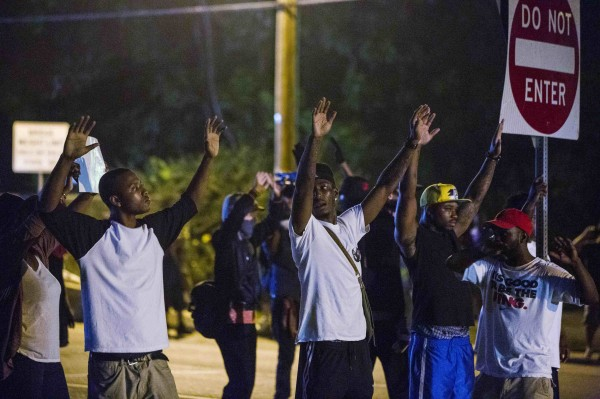 Demonstrators stand in the middle of West Florissant holding a street sign, with their hands up, towards the police during ongoing protests in reaction to the shooting of teenager Michael Brown in Ferguson, Missouri, August 18, 2014. Police fired tear gas and stun grenades at protesters in Ferguson after days of unrest sparked by the fatal shooting of an unarmed black teenager by a white policeman.