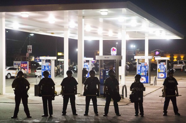 Police officers stand guard at a gas station after protests against the shooting of Michael Brown turned violent near Ferguson, Missouri August 17, 2014. Shots were fired and police shouted through bullhorns for protesters to disperse, witnesses said, as chaos erupted Sunday night in Ferguson, Missouri, which has been racked by protests since the unarmed black teenager was shot by police last week.