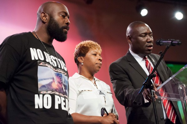 Lesley McSpadden (C) and Michael Brown Sr. (L), parents of 18-year-old Michael brown, listen while the family's attorney Benjamin Crump speaks during a rally convened in reaction to the shooting of their son, in Ferguson, Missouri August 17, 2014.