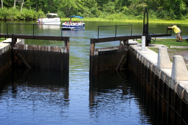 Tim Smith and Lauren Hiller swing the downriver gate open on the Songo Lock on Tuesday in Naples.