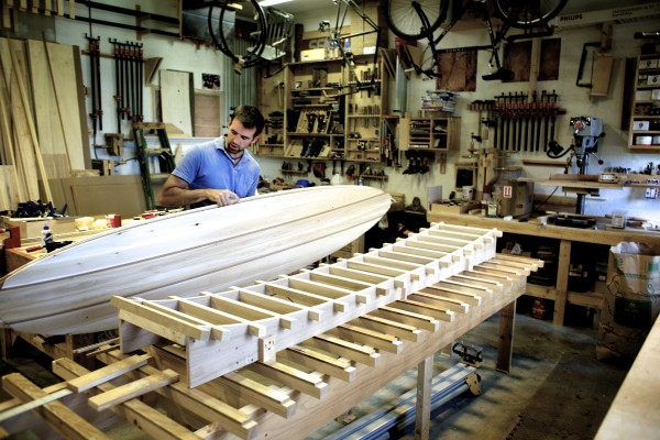 Luke Cushman looks through a hollow wood surfboard that he's making in his shop in Old Town. He builds his surfboards on rocker tables, the structure in the foreground, that match the contour of surfboards rocker or the shape of the curve on the underside of the board.